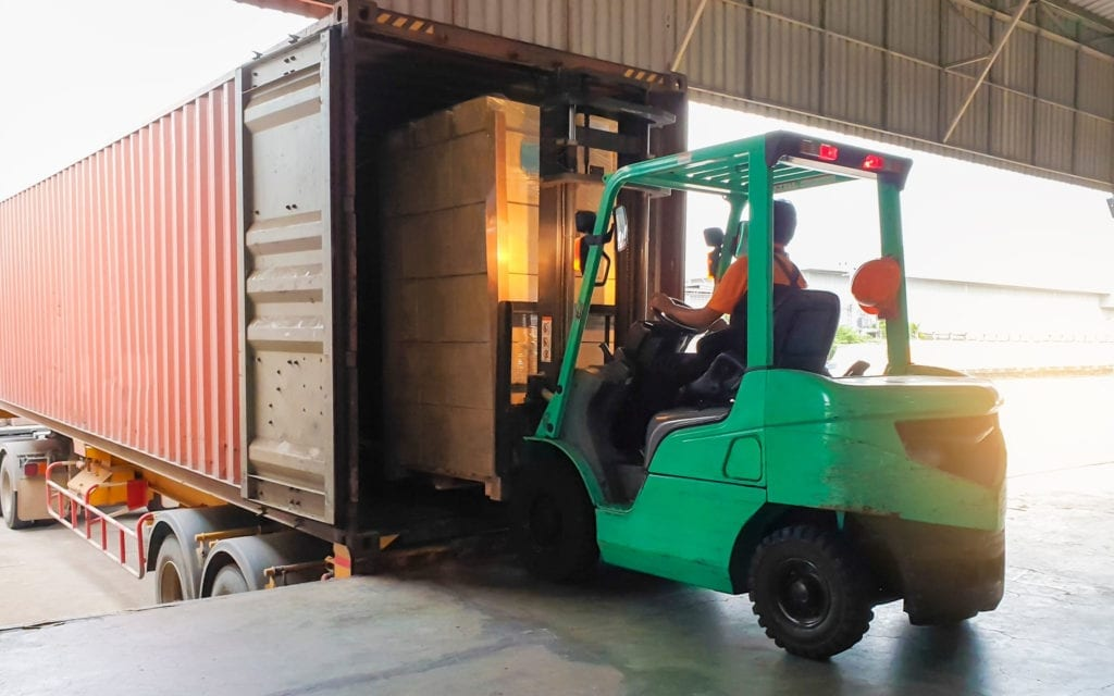 large container being unloaded by a forklift