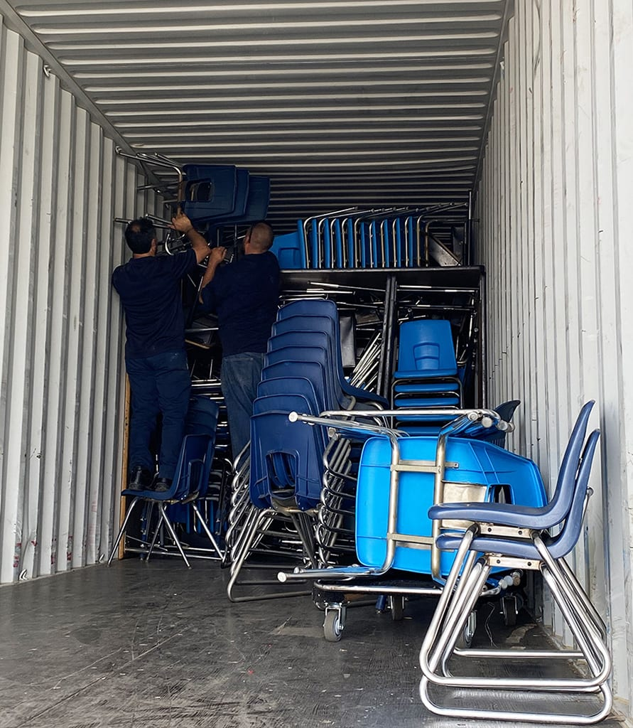 movers loading container with furniture