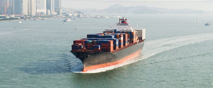 large container ship traveling on waterway near city